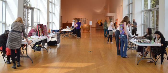 Artists sitting behind tables at the Harn Museum of Art show their touchable artwork to visually impaired visitors.