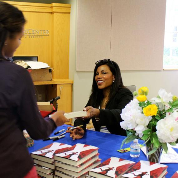 ilyasah shabazz signs her book.