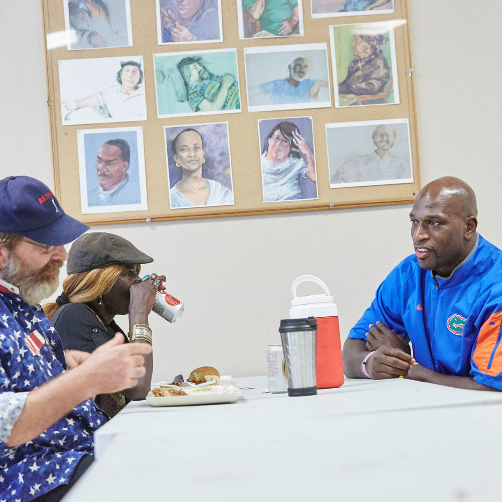 University of Florida football Hall of Famer Thaddeus Bullard, aka WWE Superstar Titus O'Neil, spent Friday morning visiting guests and helping to provide meals at St. Francis House, which serves the homeless in Gainesville.