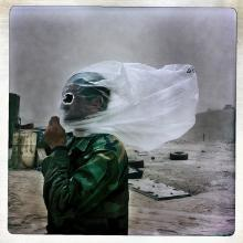An Afghan National Army soldier protects his face with a plastic bag against a dust storm at Combat Outpost 7171 in Helmand Province, Afghanistan, on Oct. 28, 2010.