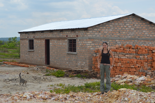 Leandra Merz in front of a brick building in Zambia