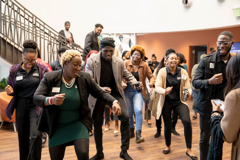 A group of people dances inside the new Institute of Black Culture building