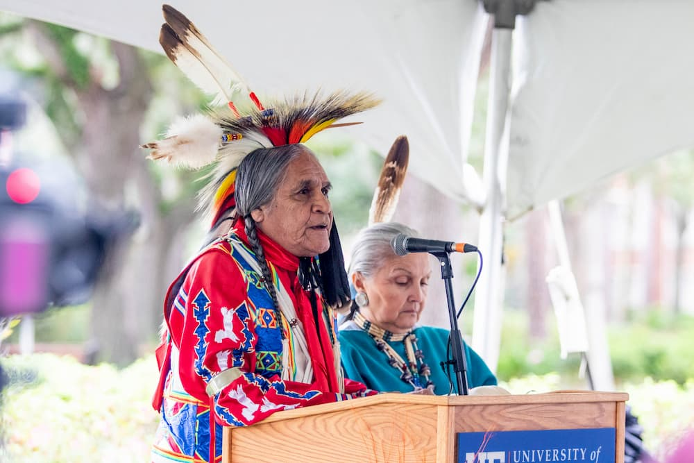 Man wearing traditional Kiowa clothing speaks at a lectern.