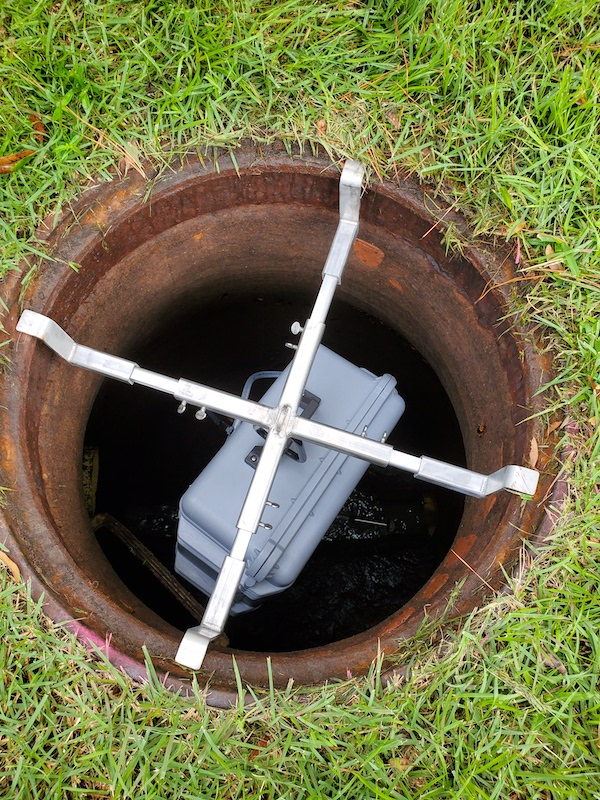 a plastic box that samples wastewater hangs in a manhole