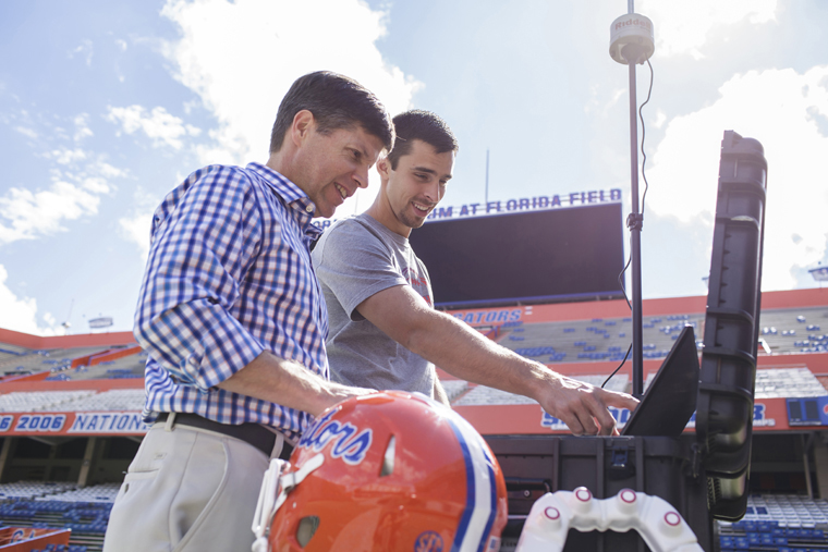 Dr. James Clugston (left) and Matt Graham, coordinator for the head impact telemetry system at UF, set up the system inside Ben Hill Griffin Stadium. The HITS system allows team physicians to monitor hits players receive on the field using sensors placed inside their helmets.
